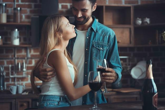 Mooie jonge paar is wijn drinken en glimlachen tijdens het koken in de keuken thuis.