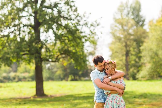 Mooie jonge paar knuffelen in het park.