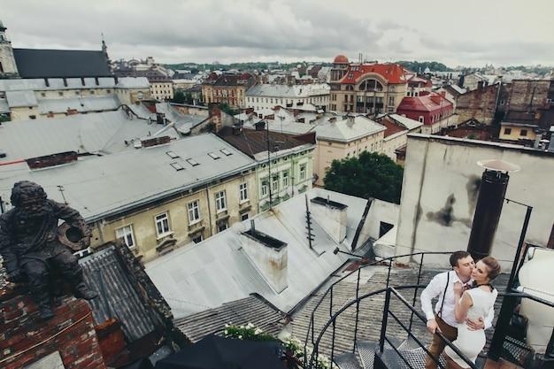 Mooie jonge paar kusjes op spiraalvormige trap op het dak