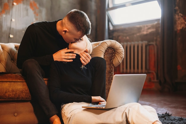 Mooie jonge paar kussen terwijl de mens op een bank zit en een meisje op de vloer thuis aan een laptop werkt.