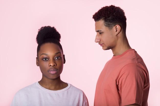 Mooie jonge paar man en vrouw op roze achtergrond