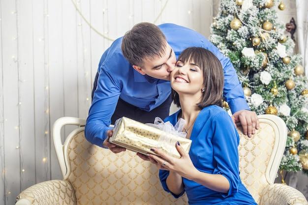 Mooie jonge paar man en vrouw samen in de gelukkige kerst?