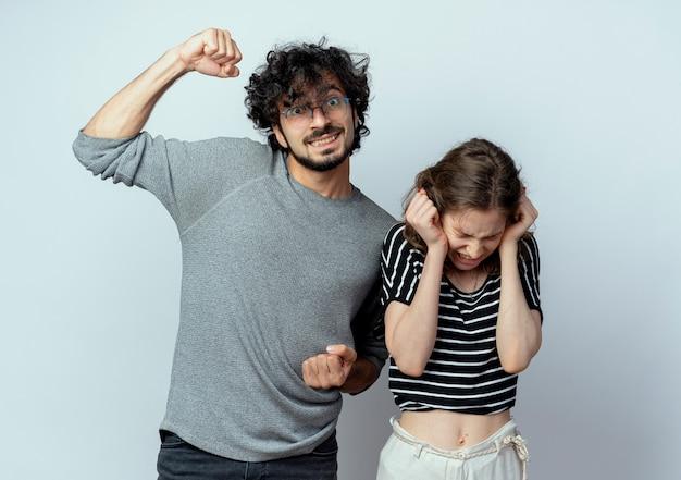 Mooie jonge paar man verhogen vuist staande naast zijn girlfrined haar oren sluiten met handen met geïrriteerde uitdrukking op witte muur