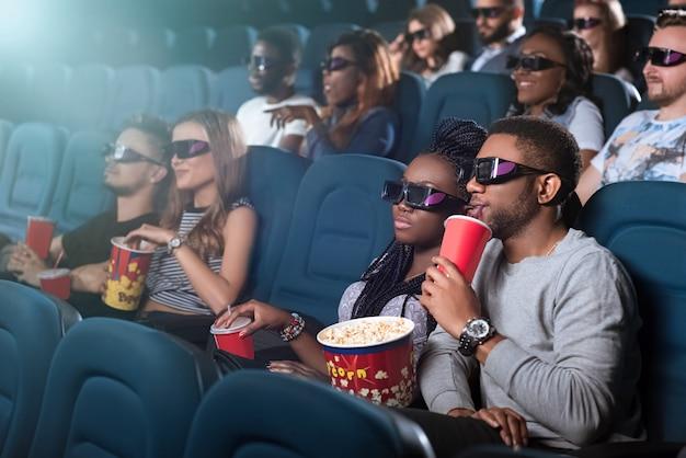 Mooie jonge paar met een date in de bioscoop kijken naar een film samen met 3d-bril