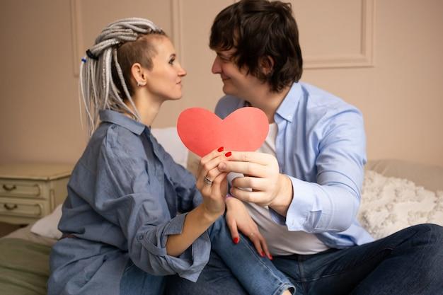 Mooie jonge paar met rood hart valentijn in slaapkamer knuffelen op bed. samen tijd doorbrengen. valentijnsdag vieren.
