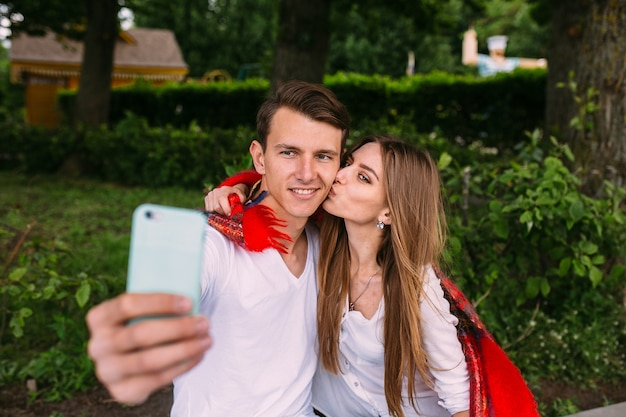 Mooie jonge paar ontspannen in het park en maakt selfie