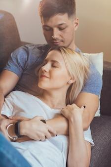 Mooie jonge paar ontspannen op de bank na het werk terwijl de vrouw leunt op de borst van haar vriendje met gesloten ogen glimlachend.