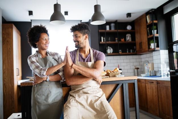 Mooie jonge paar samen gezond eten thuis koken. lekker bezig in de keuken.