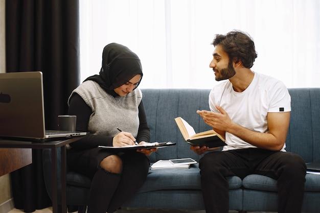 Mooie jonge paar schrijven in een notitieblok, zittend op couck thuis. arabisch meisje dat zwarte hidjab draagt.