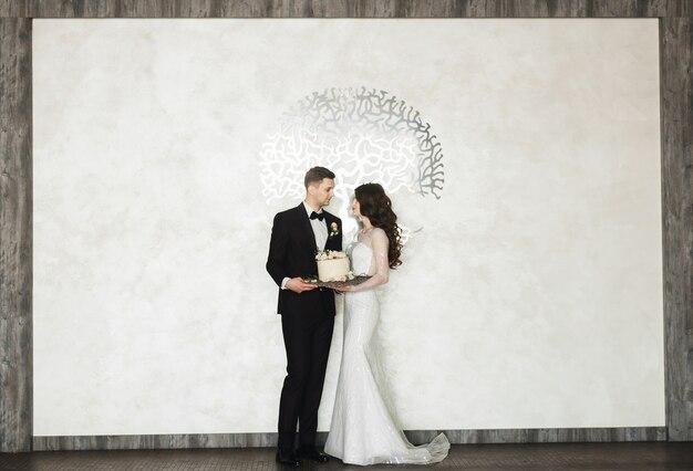 Mooie jonge paar staan en houden een bruidstaart met luxe interieur