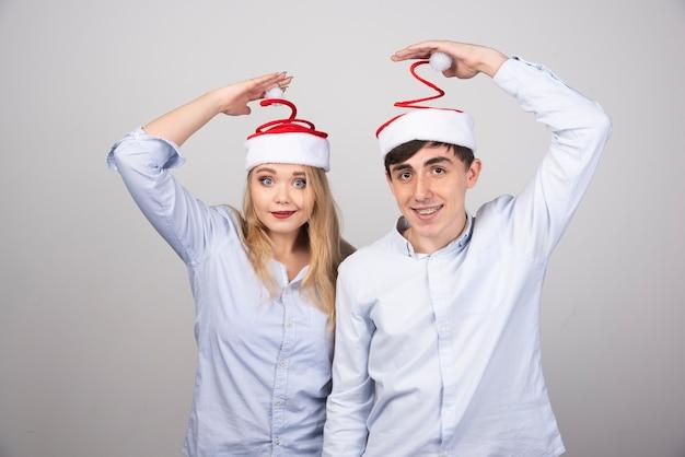 Mooie jonge paar staande in santa hoeden op grijze muur.