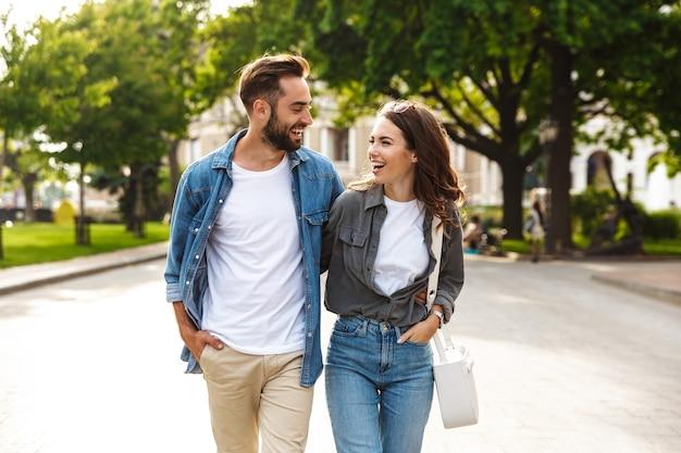 Mooie jonge paar verliefd buiten wandelen in de stad straat, knuffelen