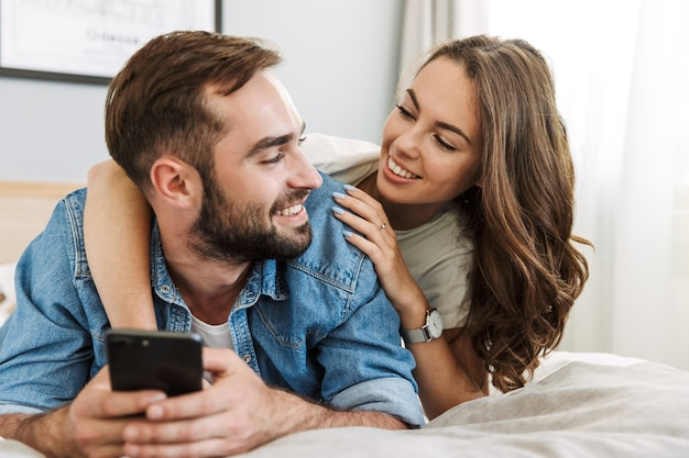 Mooie jonge paar verliefd thuis, liggend in bed, met behulp van mobiele telefoons
