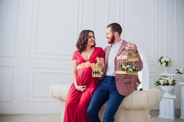 Mooie jonge paar verliefd. zwangere vrouw met haar echtgenoot om thuis te zitten. ze glimlachen en kijken naar de camera. de man heeft de sleutels van het appartement en het vogelhuisje van het meisje.