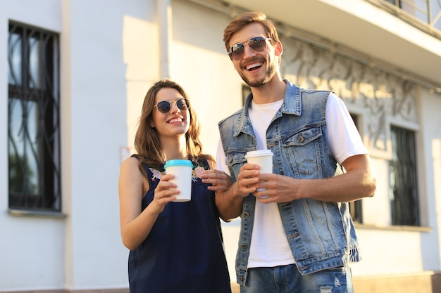 Mooie jonge paar wandelen door de stad straat, glimlachend en koffie drinken uit papier beker.
