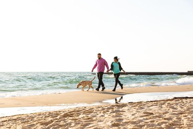 Mooie jonge paar wandelen met hun hond op het strand