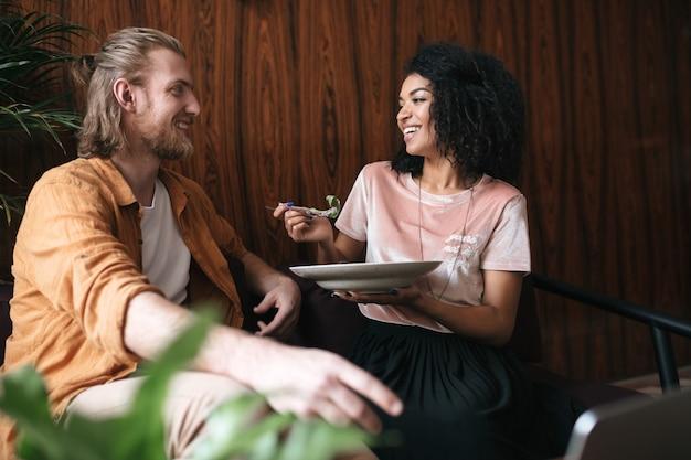 Mooie jonge paar zitten en gelukkig praten in restaurant. vrij african american lady zitten in het café met een bord salade in de hand
