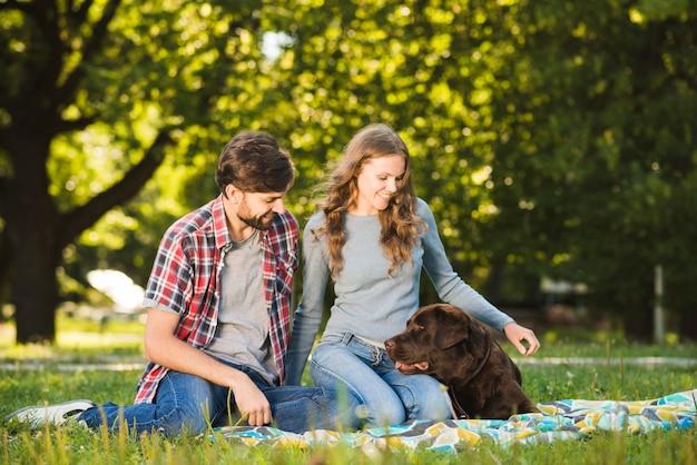 Mooie jonge paar zitten met hun hond in de tuin