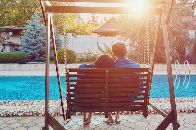 Mooie jonge paar zittend op de bank bij het zwembad
