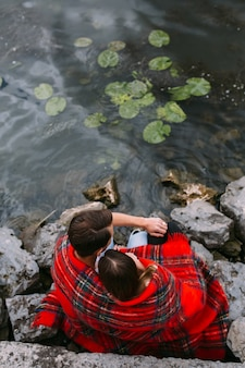Mooie jonge paar zittend op een stenen dijk, gewikkeld in een deken