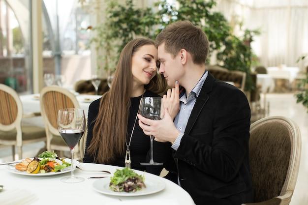 Mooie jonge paar zoenen in restaurant