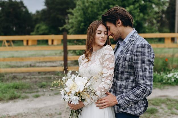 Mooie jonge paarbruid en bruidegom die dichtbij de houten omheining lopen
