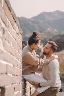 Mooie jonge paarzitting en het tonen van affectie bij de grote muur van china.
