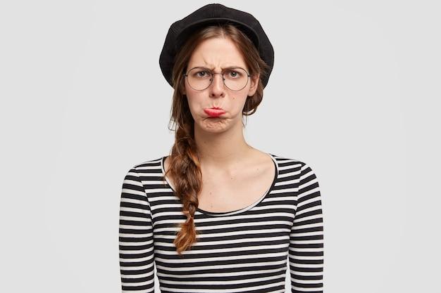 Mooie jonge parijse vrouw wordt misbruikt door negatief nieuws, portemonnees onderlip, draagt vrijetijdskleding in franse stijl