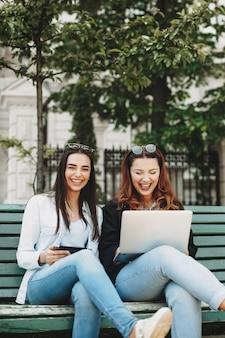 Mooie jonge plus size meisje met rood haar lachen tijdens het kijken naar haar laptop in de buurt van haar brunette vriendin die camera lachen op een bankje kijkt.