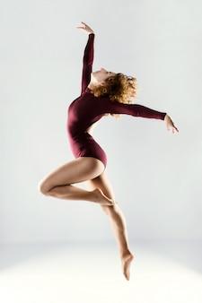 Mooie jonge professionele danser die over witte achtergrond danst.