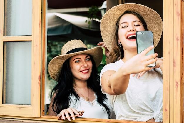 Mooie jonge ronde meisjes hebben veel plezier samen in vriendschap die selfie foto's maken met moderne telefoon