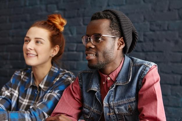 Mooie jonge roodharige blanke vrouw met haarbroodje ontspannen bij coffeeshop