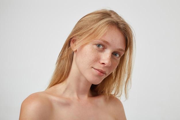 Mooie jonge roodharige langharige vrouw met casual kapsel die haar lippen gevouwen houdt terwijl ze zachtjes kijkt, poseren over een witte muur met blote schouders