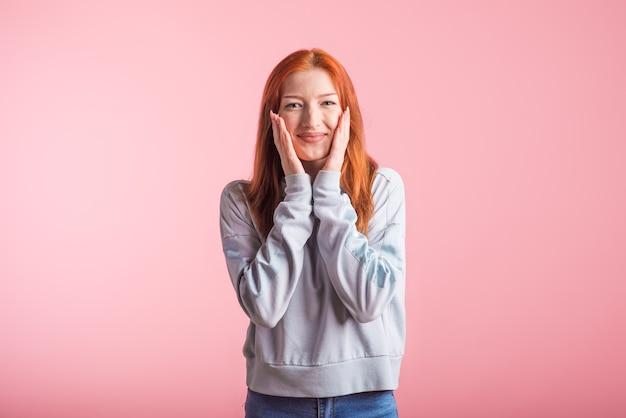 Mooie jonge roodharige meisje in de studio op een roze achtergrond