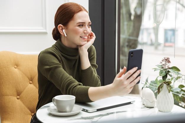 Mooie jonge roodharige vrouw die binnen aan de cafétafel ontspant, koffie drinkt, op een laptop werkt, videogesprek heeft