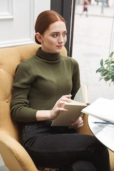 Mooie jonge roodharige vrouw die binnenshuis aan de cafétafel ontspant, koffie drinkt, een boek leest