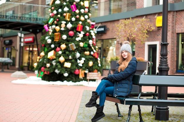 Mooie jonge roodharige vrouw die winteroutfit draagt, poserend op de achtergrond van kerstsparren