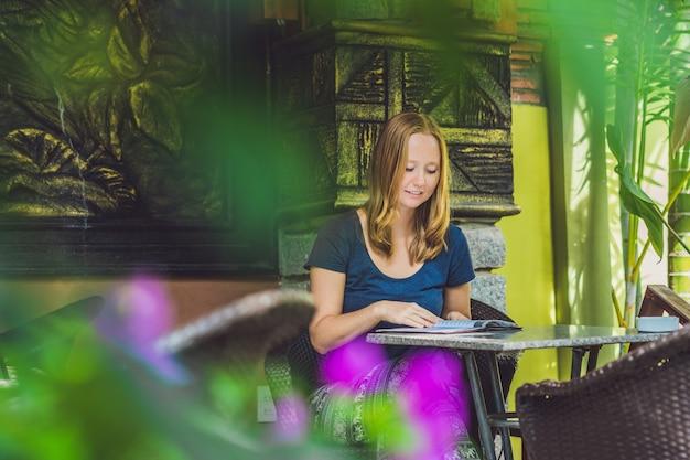 Mooie jonge roodharige vrouw in een groene hoek onderzoekt het menu van een gezellig restaurant en kiest heerlijk eten en drinken