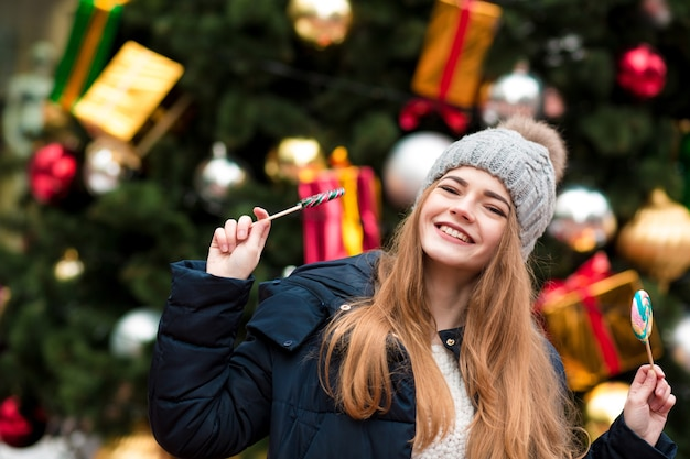 Mooie jonge roodharige vrouw in grijze gebreide muts met heerlijke karamelsnoepjes tegen kerstspar