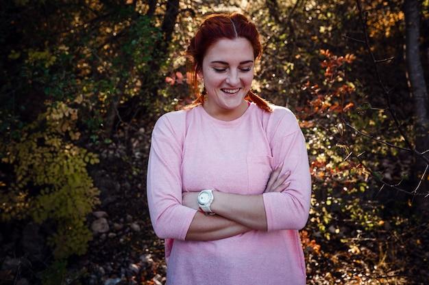 Mooie jonge roodharige vrouw in het herfstbos. idee en concept van vrije tijd, geluk, zorg en vrijheid, buitenactiviteiten en een gezonde levensstijl