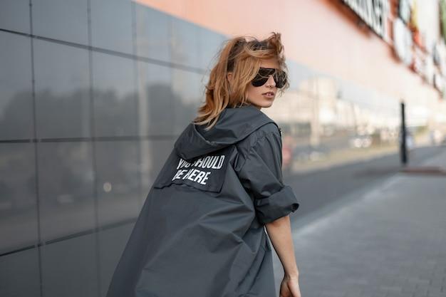 Mooie jonge roodharige vrouw in trendy zwarte zonnebril in een stijlvolle lange mode jas loopt door de stad in de buurt van een grijs gebouw. modern aantrekkelijk meisje gaat en draait zich om.