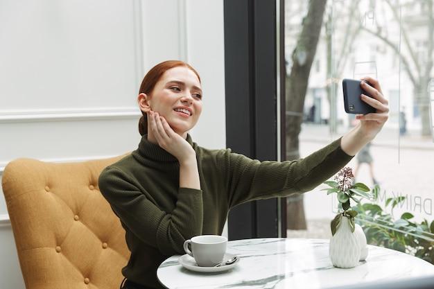 Mooie jonge roodharige vrouw ontspannen aan de cafétafel binnenshuis, koffie drinken, een selfie nemen