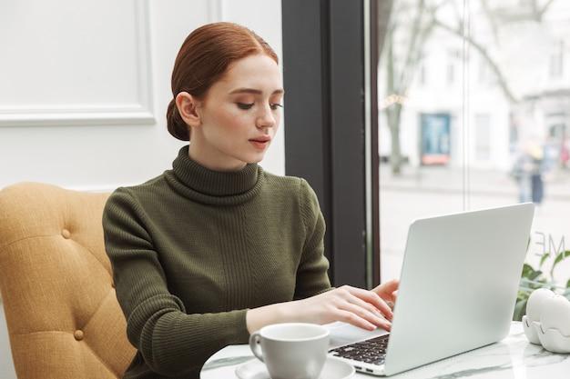 Mooie jonge roodharige vrouw ontspannen aan de cafétafel binnenshuis, koffie drinken, werken op laptopcomputer