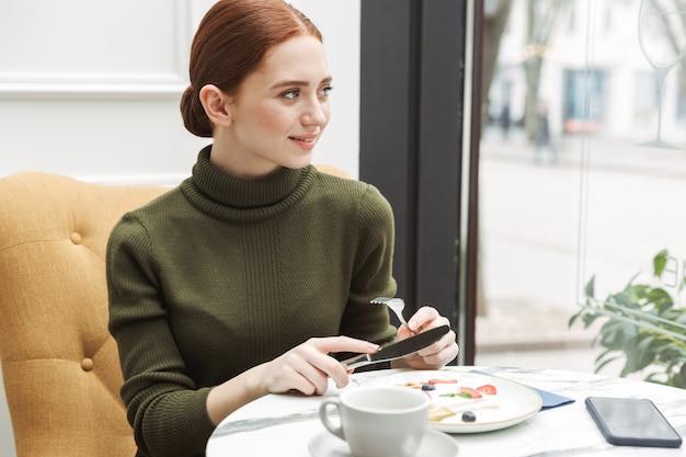 Mooie jonge roodharige vrouw ontspannen aan de cafétafel binnenshuis, lunchen