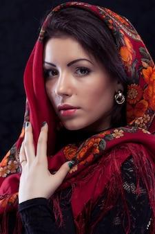 Mooie jonge russische vrouw die rode traditionele russische sjaal op zwarte achtergrond draagt