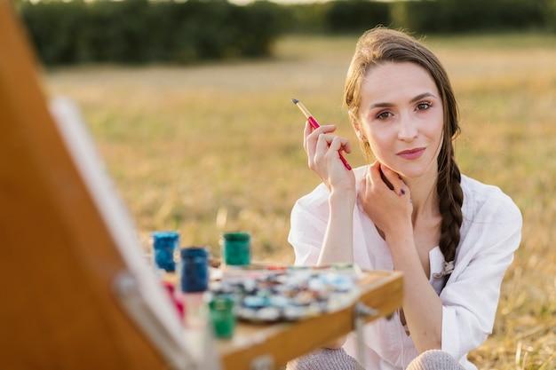Mooie jonge schilder die camera bekijkt