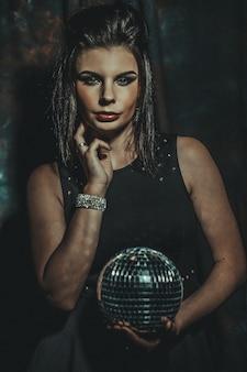 Mooie jonge sensuele vrouw met discoballen