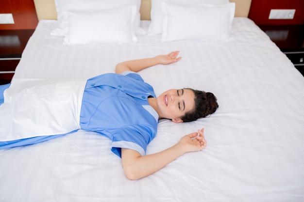 Mooie jonge serene vrouw in uniform ontspannen op wit schoon zacht bed in een van de hotelkamers terwijl u geniet van pauze
