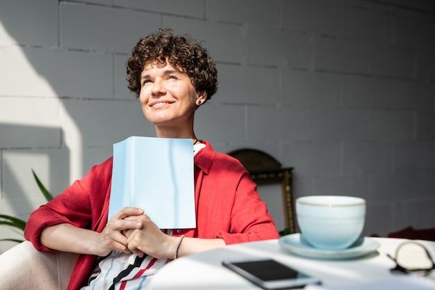 Mooie jonge serene vrouw met open boek of notitieblok geïnspireerd op zonnige dag terwijl u ontspant in café
