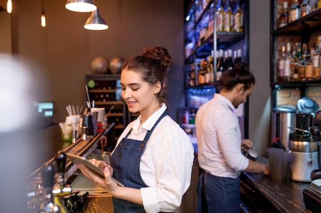 Mooie jonge serveerster met tablet scrollen door online bestellingen terwijl haar collega thee bereidt voor gasten op achtergrond